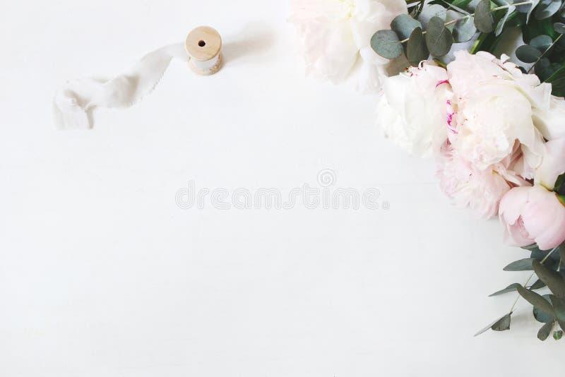 Weiblicher Hochzeits- oder GeburtstagsTabellenaufbau mit Blumenstrauß Weiße und rosa Pfingstrosenblumen, Eukalyptus und Seide lizenzfreie stockfotografie