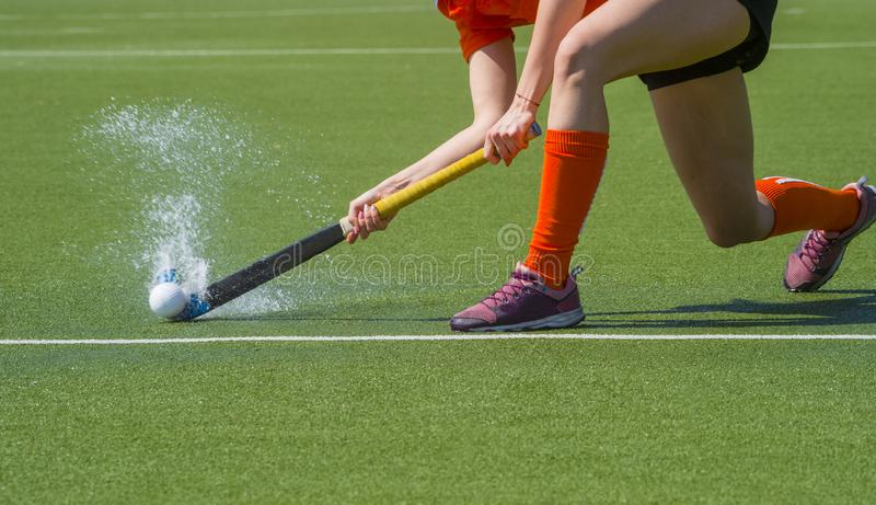 Weiblicher Hockeyspieler, der einem Teamkameraden auf einem modernen, Wasser k?nstliches astroturf Feld ?berschreitet stockbilder