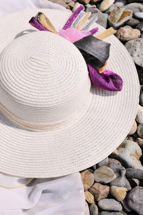 Weiblicher Hut des Strohs auf einem kieseligen Strand lizenzfreie stockfotografie