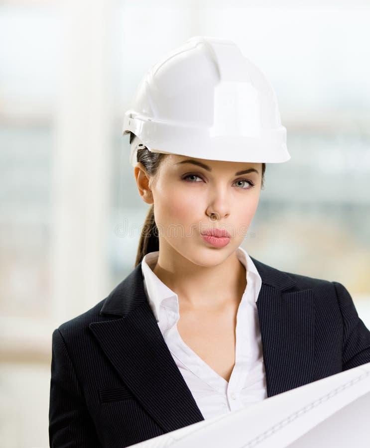 Weiblicher Ingenieur im Schutzhelm übergibt Lichtpause lizenzfreies stockbild