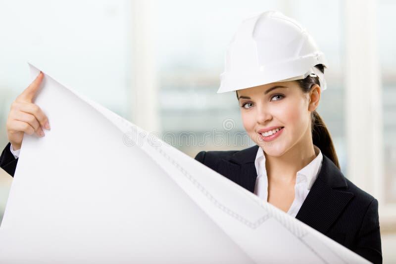 Weiblicher Ingenieur im Schutzhelm übergibt Plan lizenzfreies stockbild
