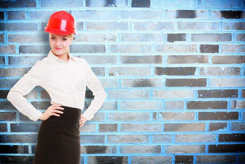 Weiblicher Ingenieurfrauenarchitekt im roten Schutzhelm und in der Backsteinmauer lizenzfreie stockfotografie