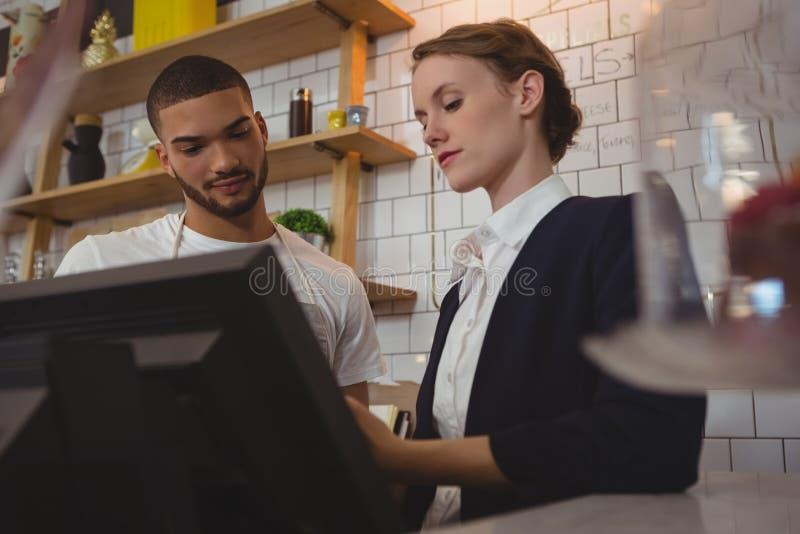 Weiblicher Inhaber mit dem Kellner, der Registrierkasse im Café verwendet stockfoto