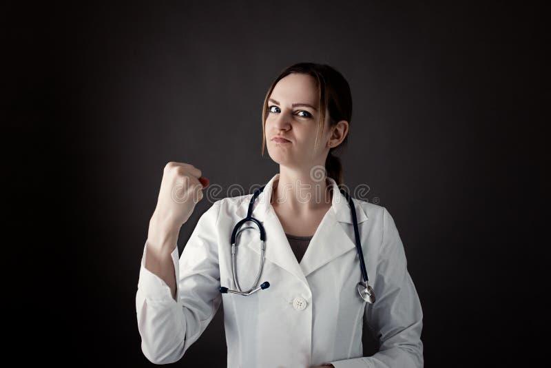 Weiblicher Internierter hält eine Faust und einen Blick in camera mit starkem Gesicht Stethoskop oder phonendoscope auf Hals Medi stockbild