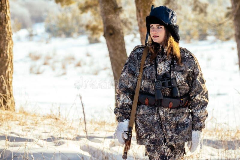 Weiblicher Jäger in der Tarnung kleidet bereites zu jagen und hält Gewehr a lizenzfreie stockfotos