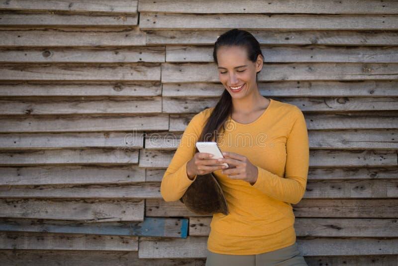Weiblicher Jockey, der intelligentes Telefon durch Stall verwendet stockfotos