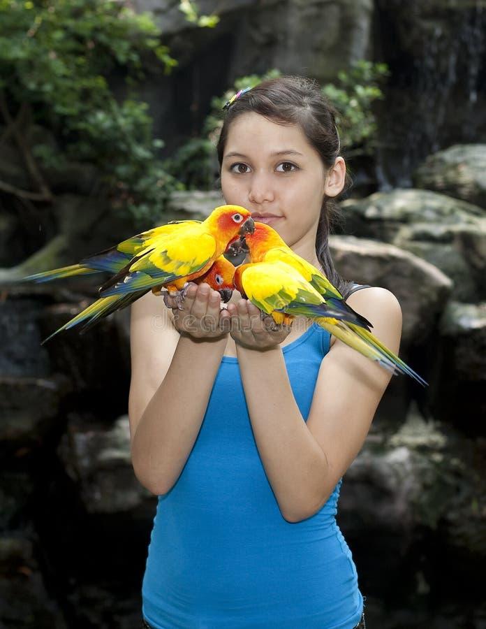 Weiblicher Jugendlicher mit Sonne conure lizenzfreie stockbilder