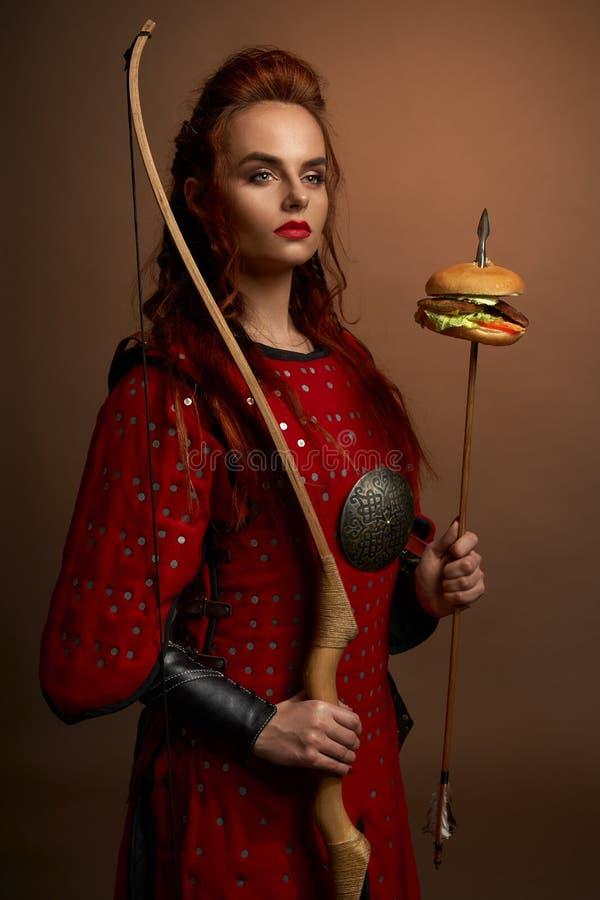 Weiblicher Kämpfer, der Pfeil und Bogen mit Hamburger hält lizenzfreie stockfotografie