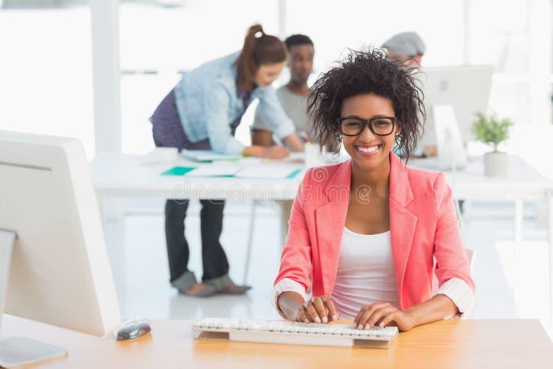Weiblicher Künstler, der Computer mit Kollegen im Hintergrund im Büro verwendet lizenzfreies stockbild
