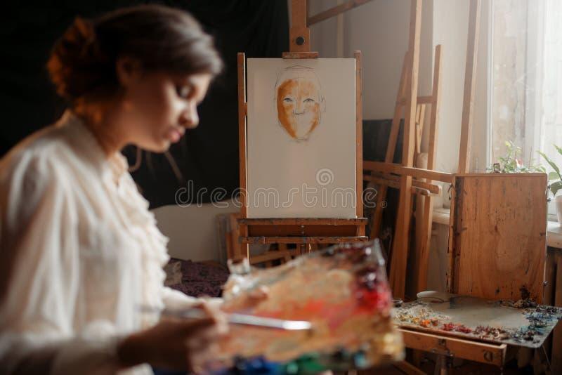 Weiblicher Künstler mit Farbpalette und -bürste stockbild