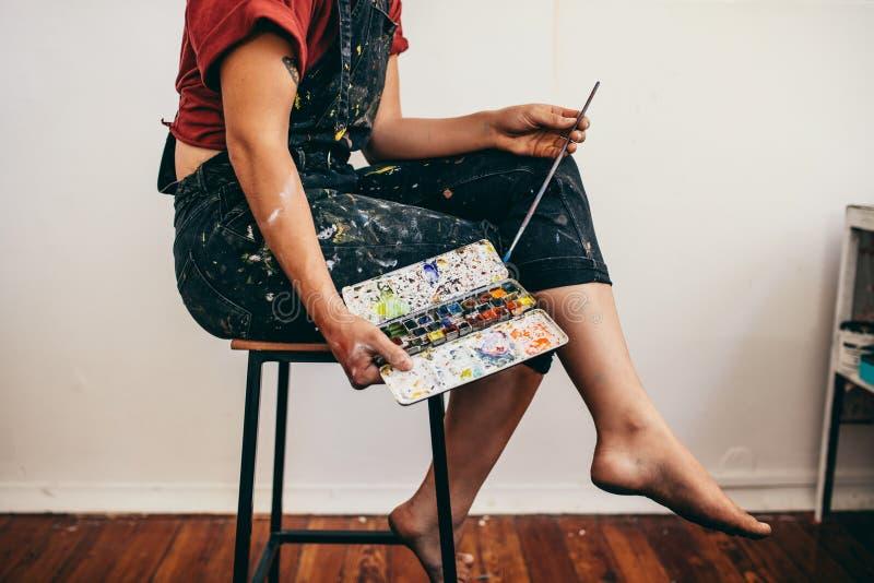 Weiblicher Künstler mit Farbpalette und -Pinsel lizenzfreie stockfotografie
