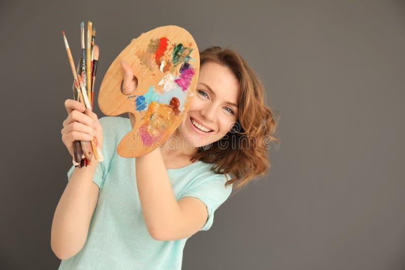 Weiblicher Künstler mit Werkzeugen und Farbenpalette auf grauem Hintergrund lizenzfreie stockfotos