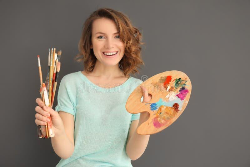 Weiblicher Künstler mit Werkzeugen und Farbenpalette auf grauem Hintergrund stockfotografie