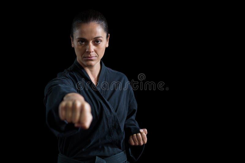 Weiblicher Karatespieler, der Karateposition durchführt lizenzfreie stockfotografie