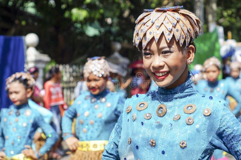 Weiblicher Karnevalstänzer in den ethnischen Kostümen tanzt in Freude entlang der Straße lizenzfreies stockbild