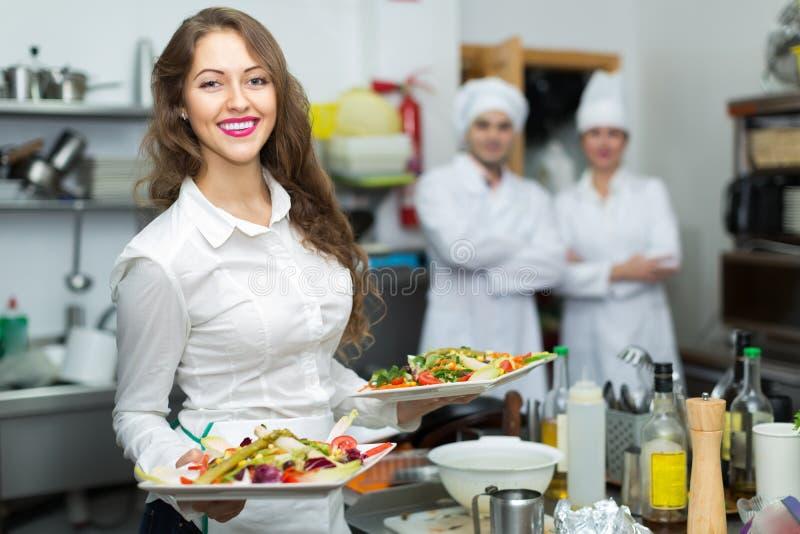 Weiblicher Kellner, der Teller an der Küche nimmt stockbild