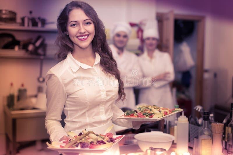 Weiblicher Kellner, der Teller an der Küche nimmt lizenzfreie stockbilder