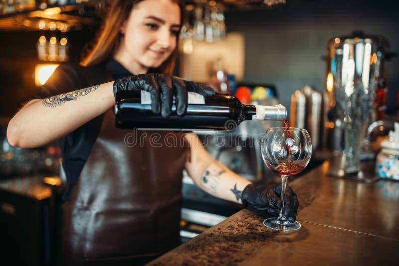 Weiblicher Kellner gießt Rotwein in ein Glas lizenzfreie stockfotografie