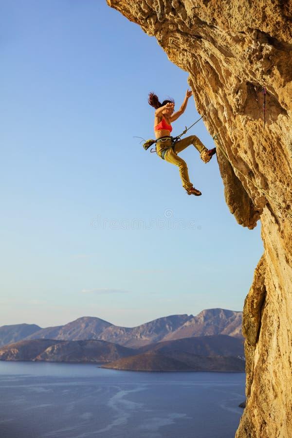 Weiblicher Kletterer, der weg Klippe fällt, während das Klettern führen Sie stockbilder