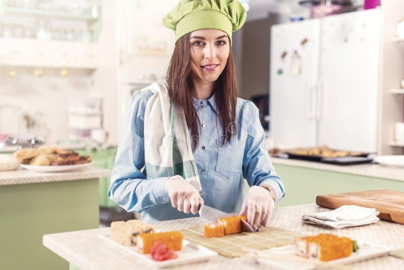 Weiblicher Koch tragender Hut und Handschuhe Chefs s, die japanische Sushirollen, Lächeln, Kamera in der Küche betrachtend machen stockfotos