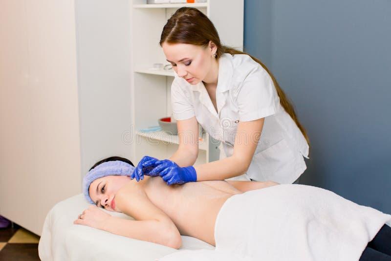 Weiblicher Kosmetikerdoktor mit Frauenpatienten in der Badekurort Wellnessmitte Berufs-massagist machen Körperrückenmassage zu stockbild