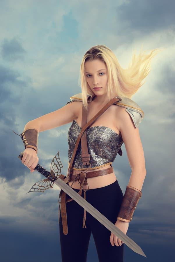 Weiblicher Krieger mit der Klinge und Haar, die im Wind durchbrennen lizenzfreie stockbilder