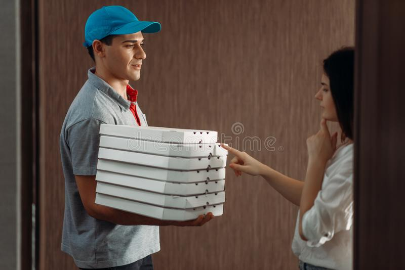 Weiblicher Kunde auf T?rstufen- und Pizzaboten lizenzfreies stockfoto