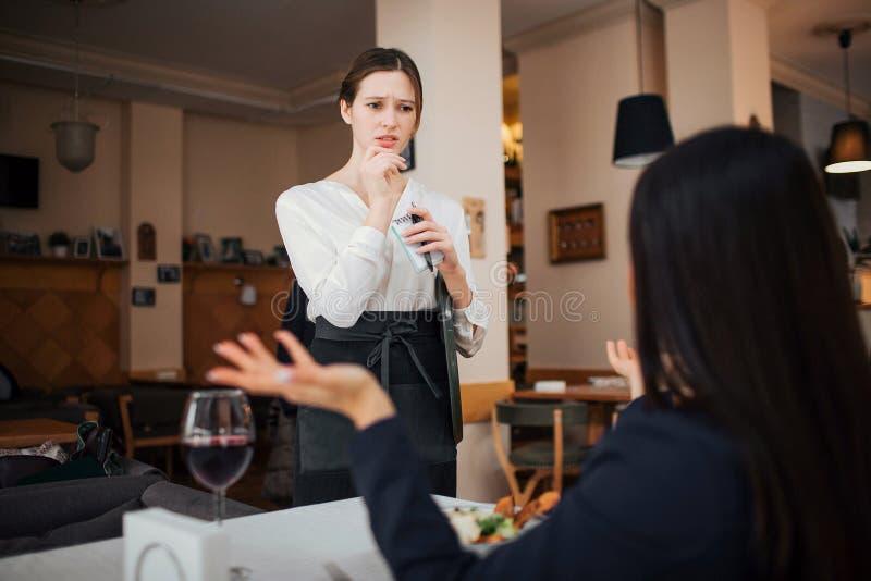 Weiblicher Kunde beschweren sich zur Kellnerin Sie hält Hände beiseite Kellnerin betrachten sie mit Interesse Sie steht bei Tisch lizenzfreie stockfotos