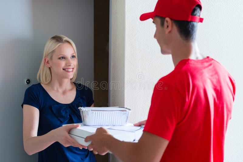Weiblicher Kunde, der den Pizzaauftrag vom Lieferer empfängt stockbild