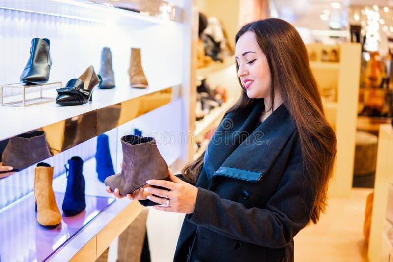 Weiblicher Kunde, der die Stiefel der Frauen in einem Speichersupermarkt wählt stockfotografie