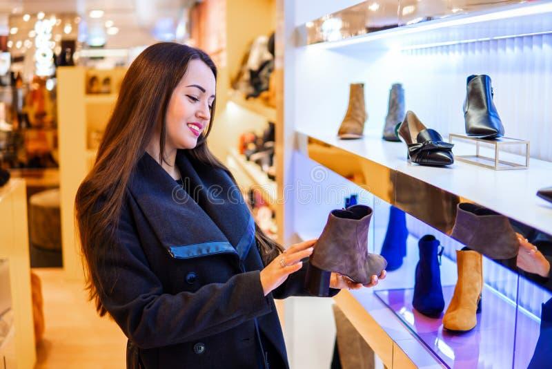 Weiblicher Kunde, der die Stiefel der Frauen in einem Speichersupermarkt wählt lizenzfreie stockfotos