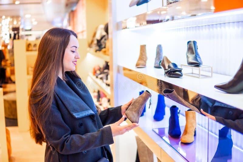 Weiblicher Kunde, der die Stiefel der Frauen in einem Speichersupermarkt wählt lizenzfreies stockbild