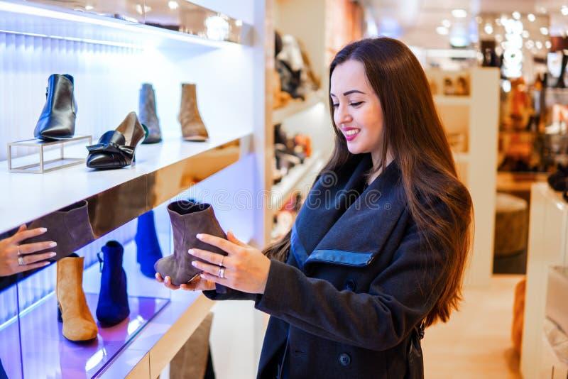 Weiblicher Kunde, der die Stiefel der Frauen in einem Speichersupermarkt wählt stockfoto