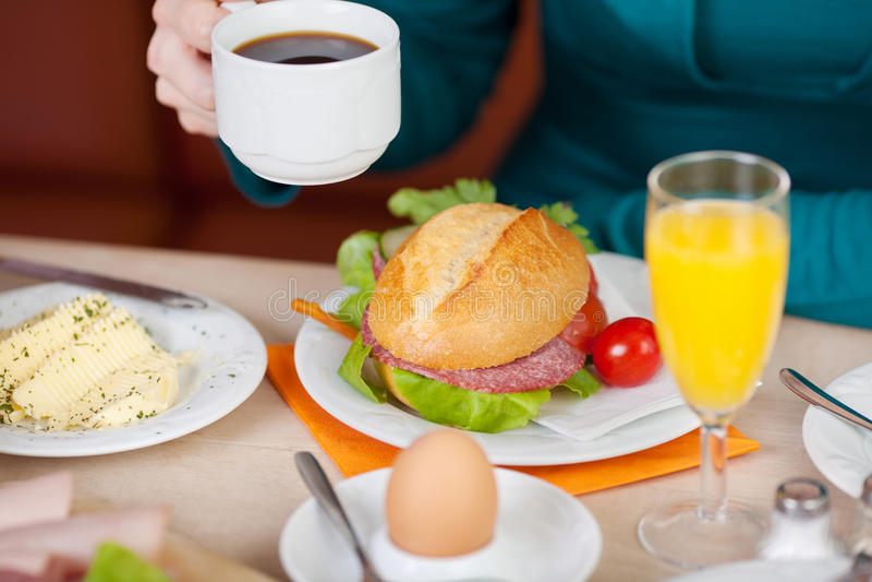 Weiblicher Kunde, der am Kaffeestube-Tisch frühstückt lizenzfreies stockbild
