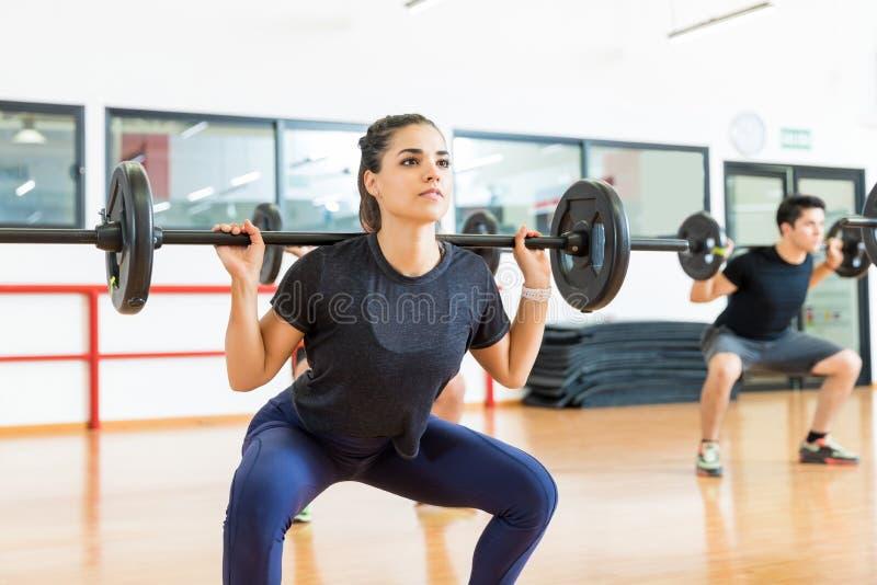Weiblicher Kunde, der mit Barbell im Fitnessstudio trainiert lizenzfreie stockfotografie
