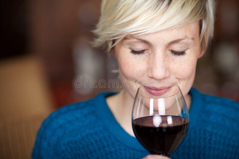 Weiblicher Kunde, der Rotwein mit den Augen geschlossen trinkt stockfotografie