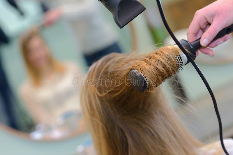 Weiblicher Kunde des trocknenden Haares des Stilisten am Schönheitssalon stockbilder