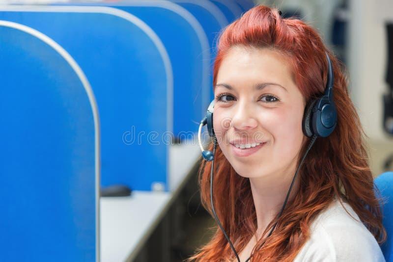 Weiblicher Kundenbetreuungsbetreiber mit dem Kopfhörerlächeln lizenzfreie stockfotografie