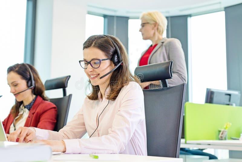 Weiblicher Kundendienstmitarbeiter unter Verwendung des Kopfhörers während Kollegen im Hintergrund im Büro lizenzfreie stockbilder