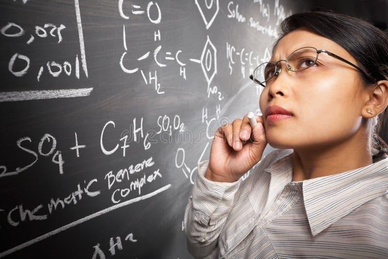 Weiblicher Kursteilnehmer, der an Gleichung arbeitet lizenzfreie stockbilder