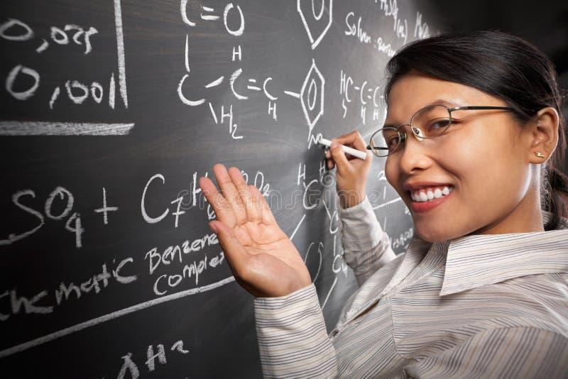 Weiblicher Kursteilnehmer, der an Gleichung arbeitet stockfoto