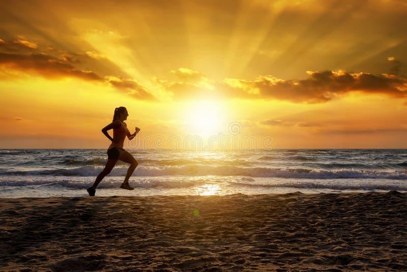 Weiblicher Läufer auf einem Strand zur Sonnenuntergangzeit lizenzfreie stockfotos