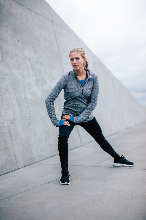 Weiblicher Läufer, der Ausdehnungen in der Stadt tut stockfotografie