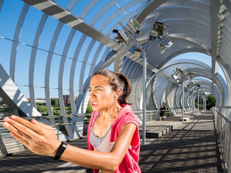 Weiblicher Läufer, der stark auf einer modernen Brücke ausbildet stockbilder