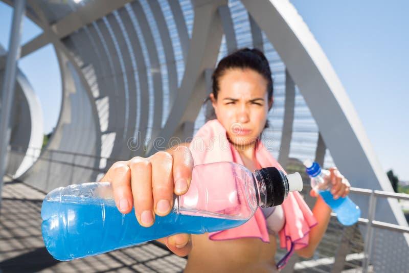 Weiblicher Läufer mit Energiegetränken für Hydratation stockbilder