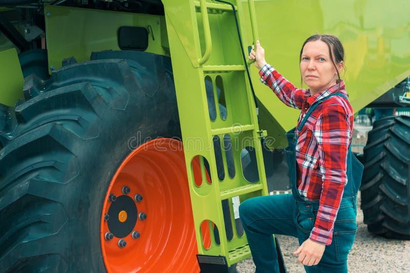 Weiblicher Landwirt, der vor M?hdrescher aufwirft stockfotografie