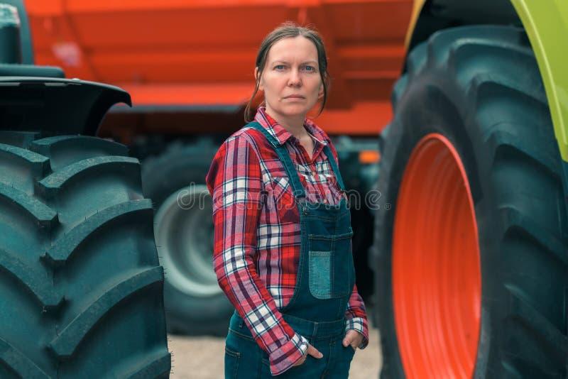 Weiblicher Landwirt und landwirtschaftlicher Traktor lizenzfreie stockbilder