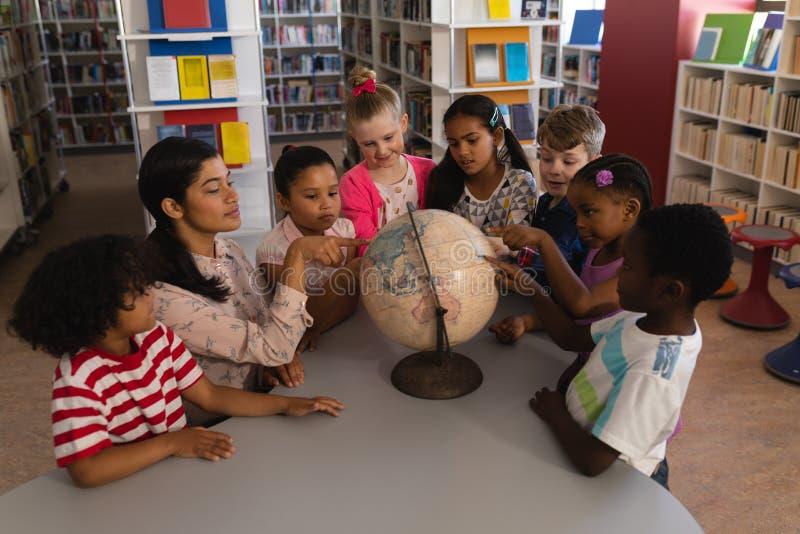 Weiblicher Lehrer, der bei Tisch die Kinder über die Kugel in der Schulbibliothek unterrichtet stockbilder