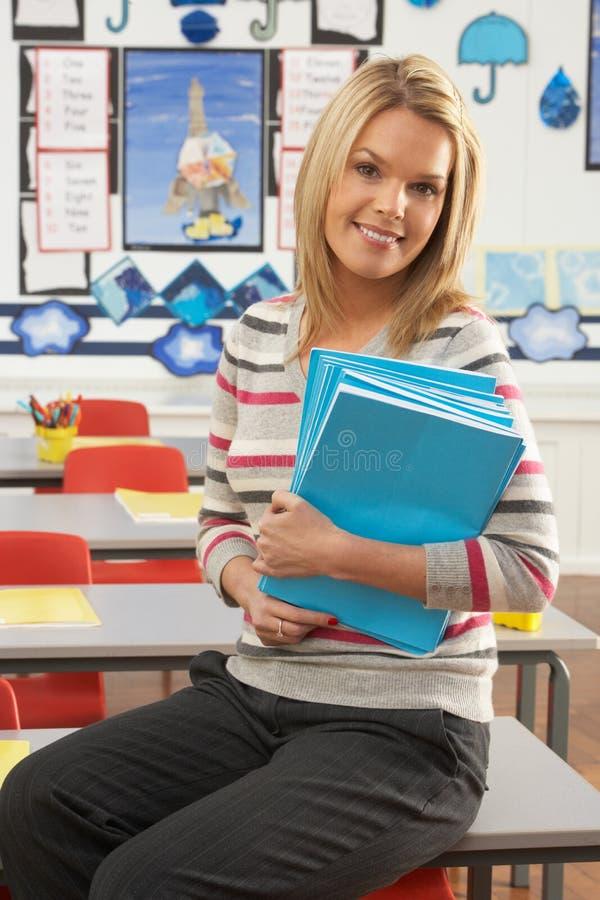 Weiblicher Lehrer, der am Schreibtisch im Klassenzimmer sitzt lizenzfreie stockfotografie