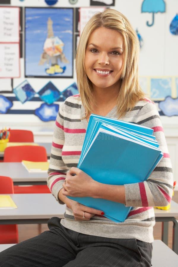 Weiblicher Lehrer, der am Schreibtisch im Klassenzimmer sitzt lizenzfreies stockbild